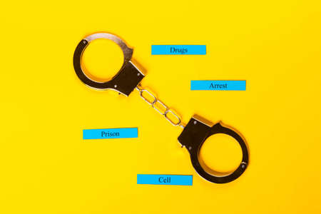 Crime concept showing handcuffs on a yellow background with Stock Photo - 123313201