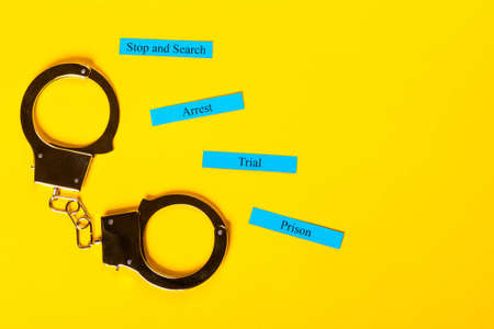 Crime concept showing handcuffs on a yellow background with Arrest Tial Prison Stop and Search