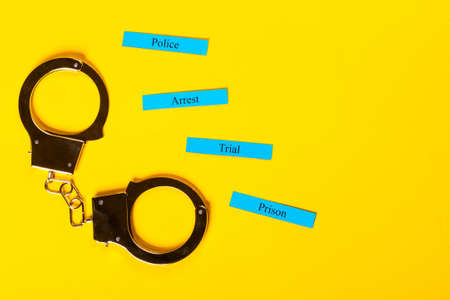 Crime concept showing handcuffs on a yellow background with Arrest Tial Prison Stock Photo - 123313205