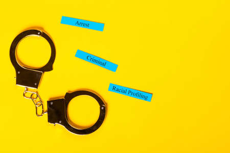 Crime concept showing handcuffs on a yellow background with Racial Profiling Stock Photo - 123313211