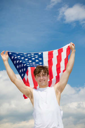 Young adult caucasian male holding on a beach holding the flag of The United States 版權商用圖片