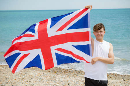 Young adult caucasian male holding on a beach holding the flag of Great Britain 版權商用圖片