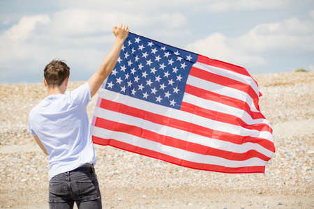 Young adult caucasian male holding on a beach holding the flag of The United States 免版税图像