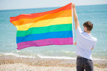 Young adult caucasian male holding on a beach holding the Pride flag Stock Photo