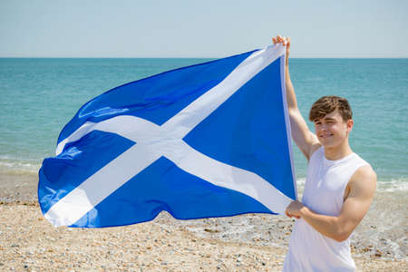 Young adult caucasian male holding on a beach holding the flag of Scotland Imagens