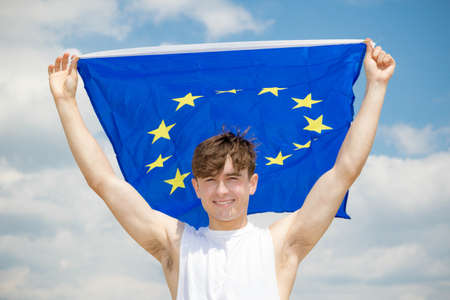 Young adult caucasian male holding on a beach holding the flag of the European Union