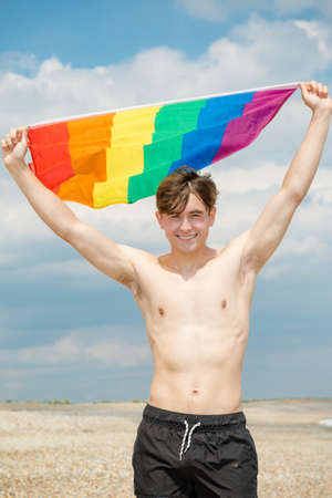 Young adult caucasian male holding on a beach holding the Pride flag Imagens