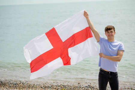 Young adult caucasian male holding on a beach holding the flag of England Imagens