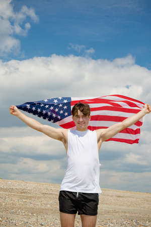 Young adult caucasian male holding on a beach holding the flag of The United States Imagens - 124883250