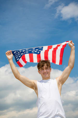 Young adult caucasian male holding on a beach holding the flag of The United States Imagens