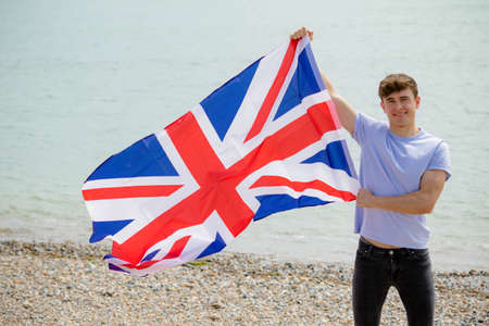 Young adult caucasian male holding on a beach holding the flag of Great Britain Imagens