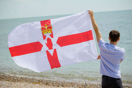 Young adult caucasian male holding on a beach holding the flag of Northern Ireland Imagens - 124883262