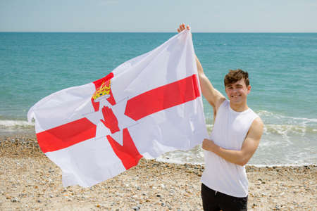 Young adult caucasian male holding on a beach holding the flag of Northern Ireland