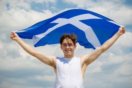 Young adult caucasian male holding on a beach holding the flag of Scotland Imagens - 124883267