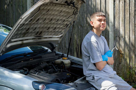 Teenage caucasian boy sitting on the front of a car with the bonnet open holding tools