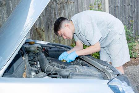 Teenage caucasian boy working on a car engine