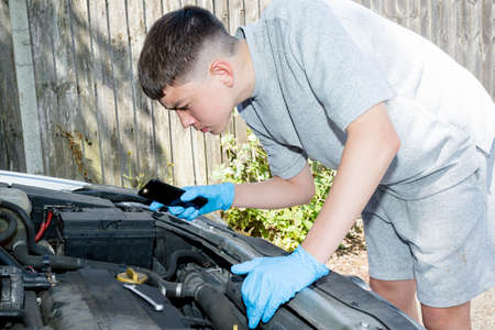 Teenage caucasian boy using a mobile phone light to work on an engine Stock fotó