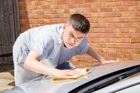Teenage boy washing a car on a warm summer's day Archivio Fotografico