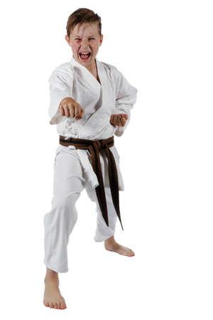 Teenage caucasian boy wearing a karate uniform doing karate