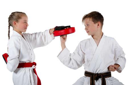 Caucasian pre-teen girl and teenage boy doing karate