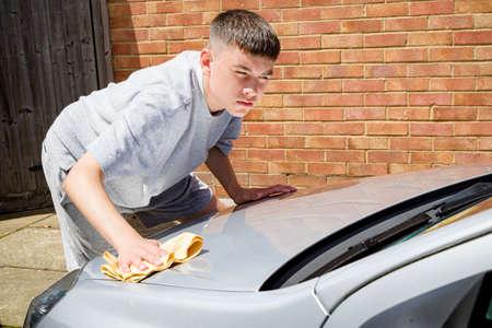 Un adolescent lave une voiture par une chaude journée d'été Banque d'images