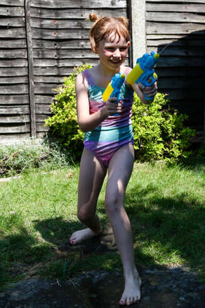 Preteen caucasian girl playing wth water guns on a hot summer's day