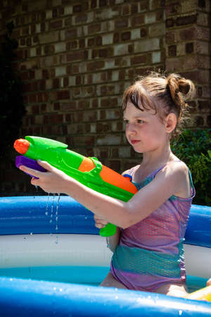 Preteen caucasian girl playing wth a water gun on a hot summer's day Archivio Fotografico - 127931273