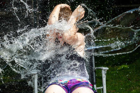 Preteen caucasian boy being splashed with water Imagens