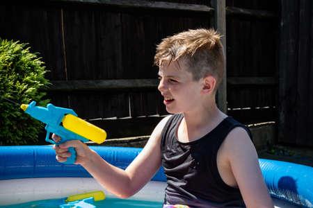 Preteen caucasian boy playing wth a water gun on a hot summer's day