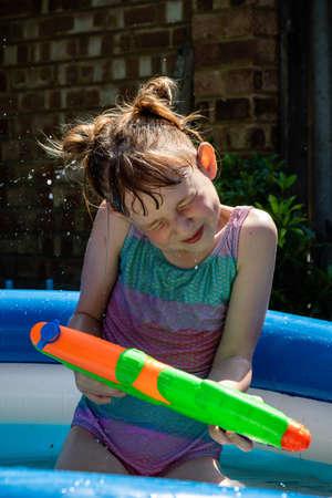 Preteen ragazza caucasica che gioca con una pistola ad acqua in una calda giornata estiva