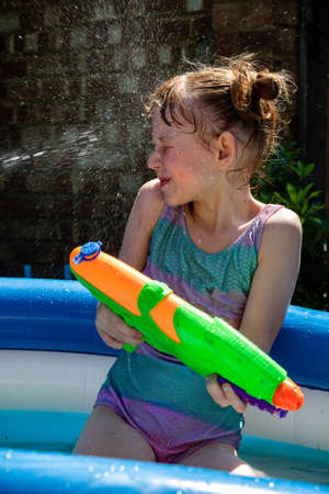 Preteen caucasian girl playing wth a water gun on a hot summer's day Stock Photo