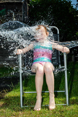 Preteen caucasian girl being splashed with water