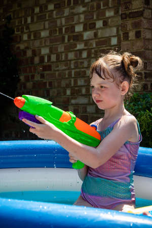 Preteen caucasian girl playing wth a water gun on a hot summer's day Archivio Fotografico - 127931082