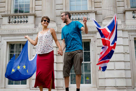 London, United Kingdom, August 31st 2019:- A man and a woman wave British and EU flags during protests against Prime Minister Boris Johnson's plan to suspend Parliament for five weeks.