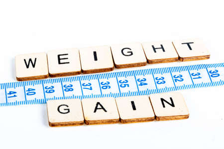 Health concept of a tape measure also showing the message Weight Gain Stockfoto