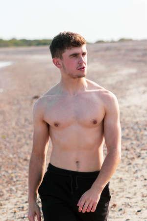 Young caucasian shirtless man wearing swimwear walking on a beach on a warm summer's afternoon Foto de archivo
