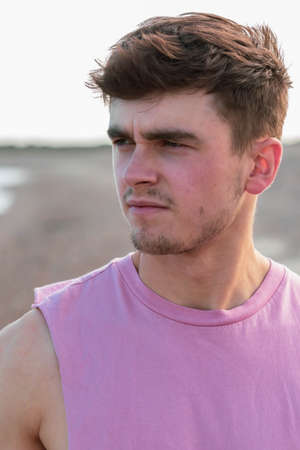 Young caucasian man walking on a beach at golden hour wearing a sleeveless shirt