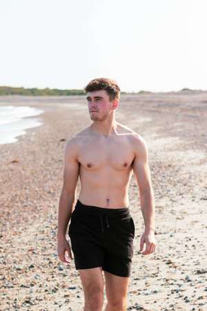 Young caucasian shirtless man wearing swimwear walking on a beach on a warm summer's afternoon Banque d'images