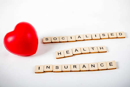 Healthcare concept showing a heart and the message socialised health insurance Stock Photo