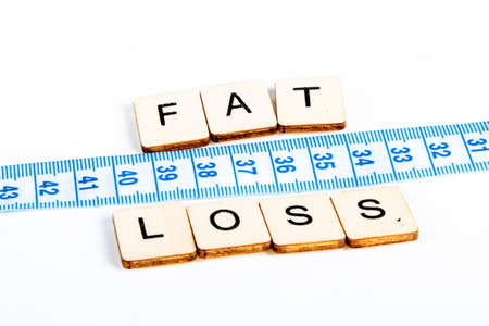 Health concept of a tape measure also showing the message Fat Loss