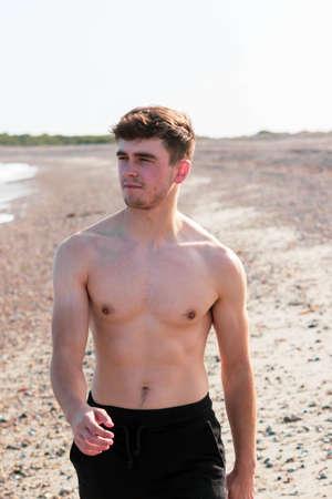Junger kaukasischer Mann mit nacktem Oberkörper in Badebekleidung, der an einem warmen Sommernachmittag am Strand spazieren geht Standard-Bild