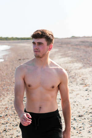Young caucasian shirtless man wearing swimwear walking on a beach on a warm summer's afternoon Reklamní fotografie