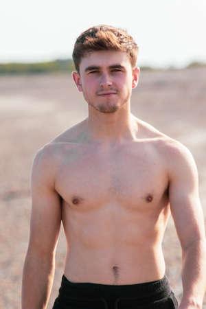 Joven caucásica sin camisa hombre vestido con traje de baño caminando por la playa en una cálida tarde de verano