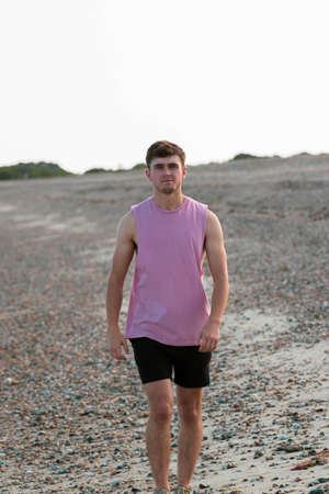 Young caucasian man walking on a beach at golden hour wearing a sleeveless shirt and black shorts Banco de Imagens
