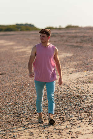 Young caucasian man walking on a beach at golden hour wearing a sleeveless shirt and jeans Banco de Imagens