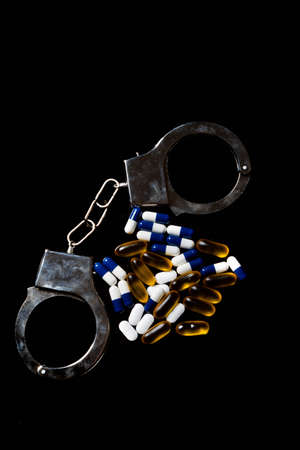 Illegal drug crisis concept showing pills and handcuffs Stock Photo