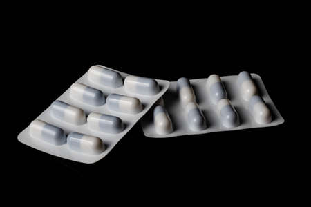 Illegal drug crisis concept showing tablets on a black background Stock Photo