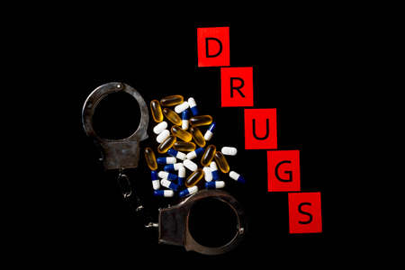 Illegal drug crisis concept showing tablets, handcuffs and the message Drugs Stock Photo
