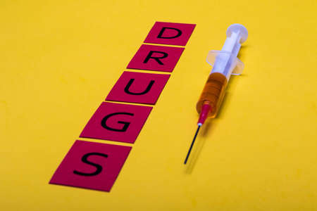 Illegal drug crisis concept showing a full syringe and the message Drugs on a yellow background