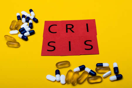 Illegal drug crisis concept showing pills and the message crisis on a yellow background